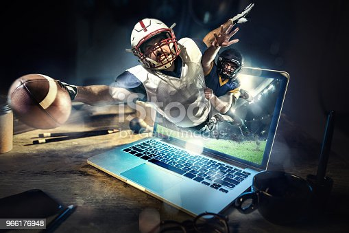 istock Collage about american football players in dynamic action with ball in a professional sport game. He playing on the laptop 966176948