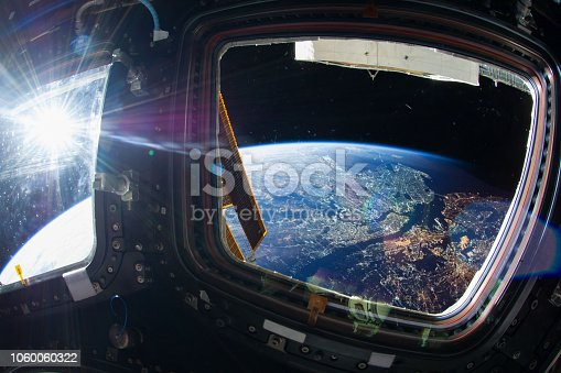 Collage image with huge NY city at night with city lights from the outer space from the ISS window. Elements of this image furnished by NASA.