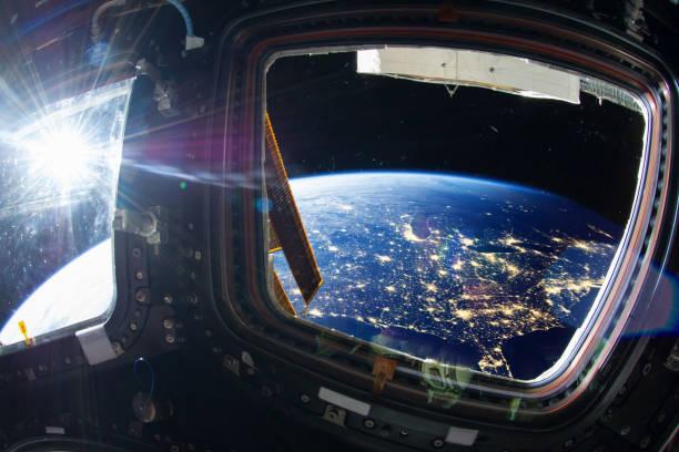 collage foto met enorme ons at night met stadslichten van de ruimte van het iss-venster. elementen van dit beeld ingericht door nasa. - ruimtevaart voertuig stockfoto's en -beelden