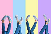 Collage of female legs in jeans and sneakers on colored background