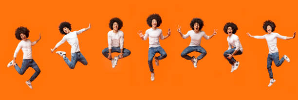 Collage of jumping bushy black guy on orange Collage of jumping bushy black guy in air on orange background, panorama sequential series stock pictures, royalty-free photos & images