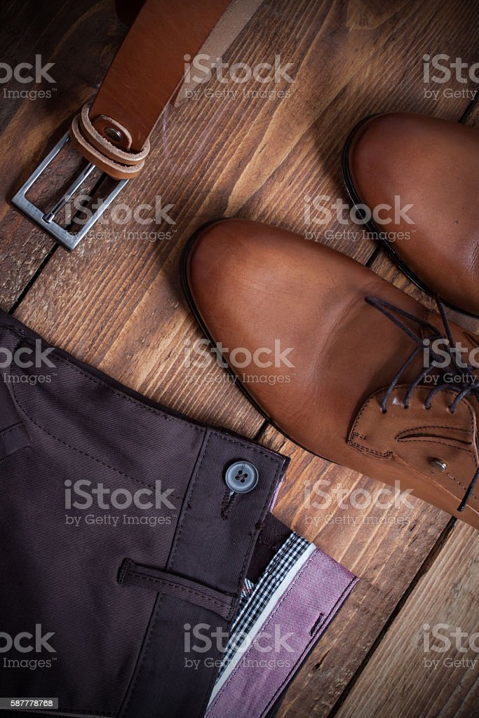Collage of modern men's clothing on a brown  wooden background. stock photo