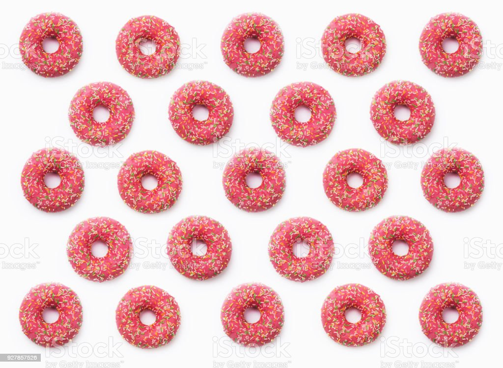Collage of pink donuts in glaze on a white background. Lots of donuts are mosaic lined, delicious fresh pink donuts are watered with glaze stock photo