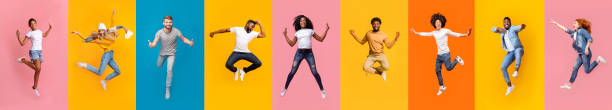 Collage of positive multiracial young people jumping over colorful backgrounds Collage of cheerful multiracial young people jumping over colorful backgrounds, panorama young adult stock pictures, royalty-free photos & images