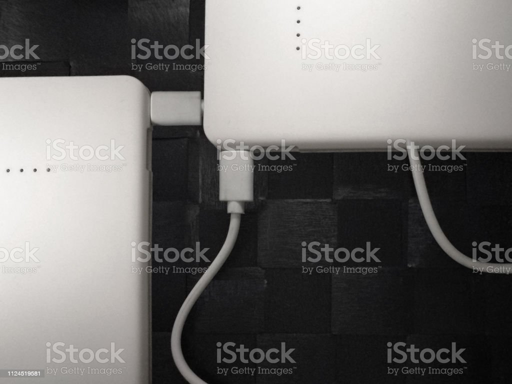 collage photo of two white power banks and usb cables on tiled small picture id1124519581
