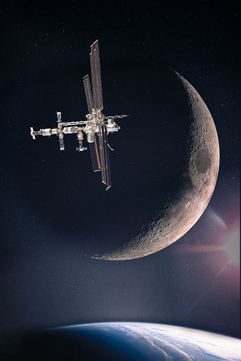 Collage with space station at the starry galaxy above the planet Earth and on the background of waxing crescent moon, elements of this image are furnished by NASA.