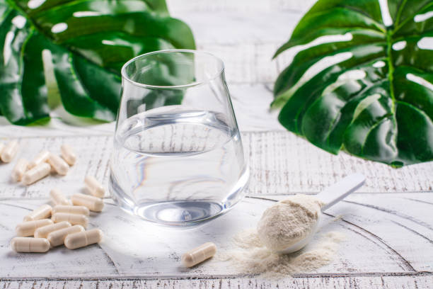 Collagen powder and pills Glass of water, collagen powder and pills on white wooden table. Healthy lifestyle concept. Copy space peptide stock pictures, royalty-free photos & images