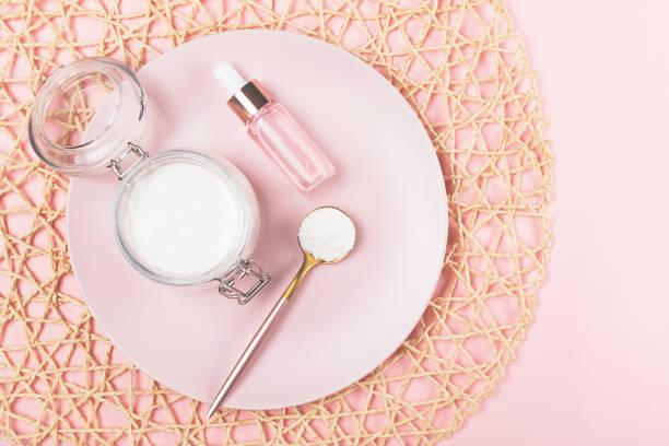 Kollagenpulver und Serumflasche auf rosa Hintergrund. – Foto