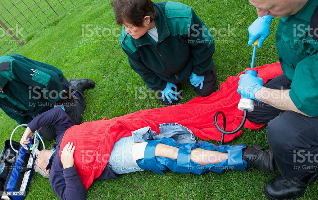 Collapsed man with leg injuries paramedics nurses in attendance stock photo
