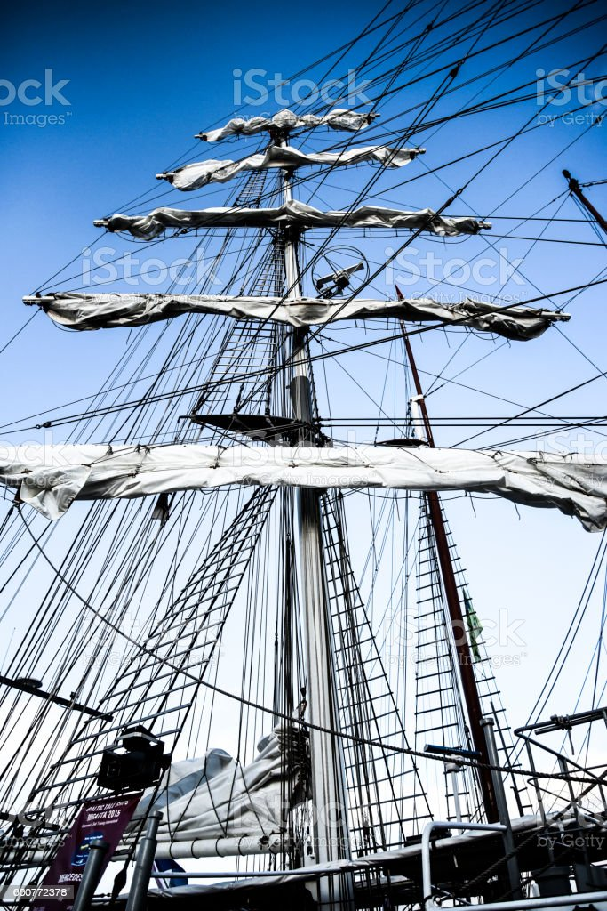 Collapsed sails on mast, big sailing yacht in harbor. stock photo