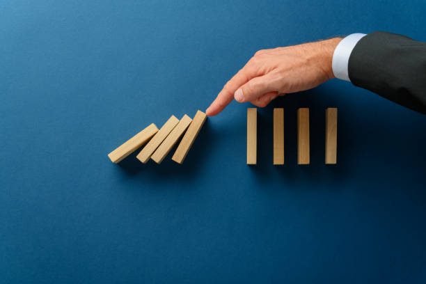 Collapsing dominos being stopped my a crisis business manager stock photo
