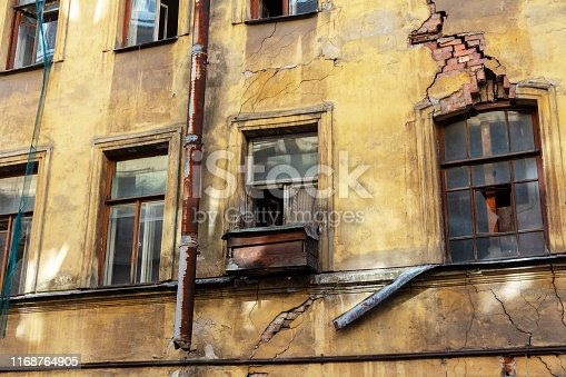 istock collapsing facade of an old building with broken windows and crack in a brick wall 1168764905