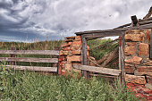 istock Collapsing Log Cabin with Window and Fence in Field 1050996848