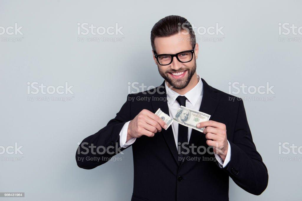 Collar modern cashback budget reduce price less interest cost customer concept. Portrait of confident smart handsome salesman holding two halves on banknote isolated on gray background stock photo