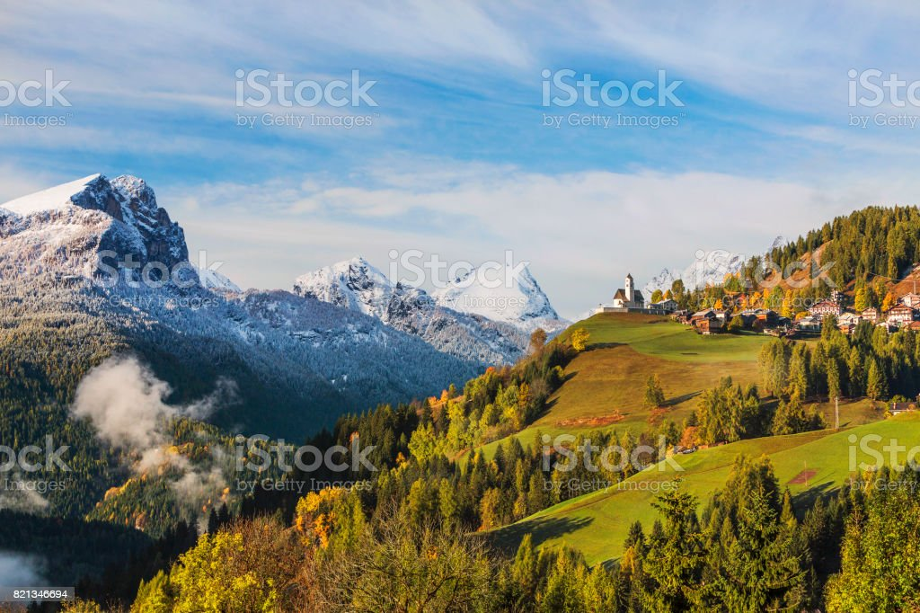 Colle Santa Lucia (Dolomites, Veneto, Italy). Picturesque autumn landscape with a church on the hill and the snow-capped mountains in Dolomites. Italy. stock photo