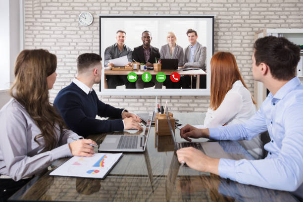 Colleague Doing Video Conferencing In Office stock photo