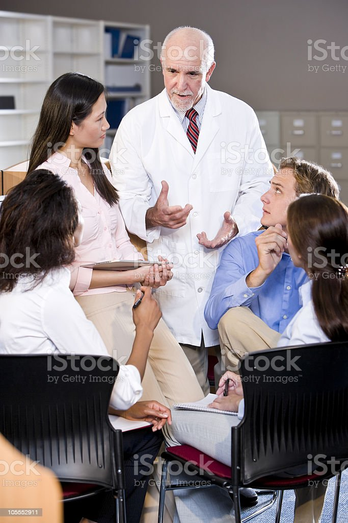 Colleague students in an ongoing discussion with a professor royalty-free stock photo