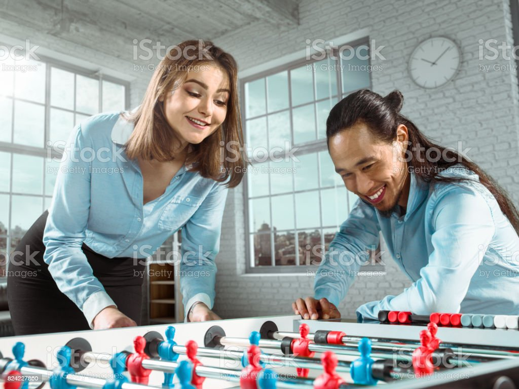 A colleague teaches a girl to play table football/kicker game in office stock photo