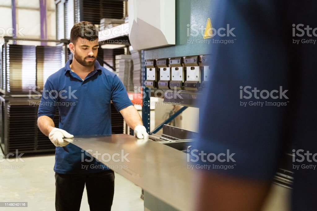 Colleagues adjusting metallic sheet in industry Colleagues adjusting metal sheet in machinery. Male engineers are working together in industry. They are wearing uniform. 20-24 Years Stock Photo