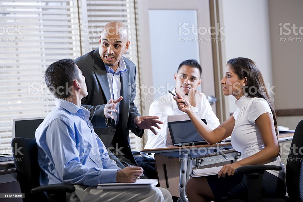 Colleagues and a manager discussing in a business setting royalty-free stock photo