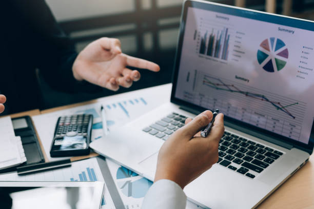 Colleagues are stress talking about the results report and compared with the financial information on the laptop screen. Colleagues are stress talking about the results report and compared with the financial information on the laptop screen. data stock pictures, royalty-free photos & images