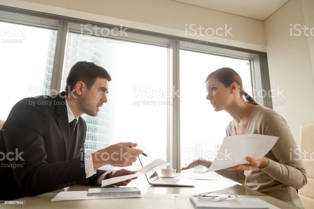 Colleagues arguing at workplace, disagree about document, error in contract stock photo