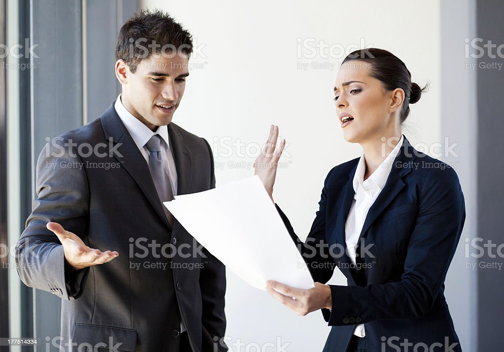colleagues arguing over paperwork stock photo