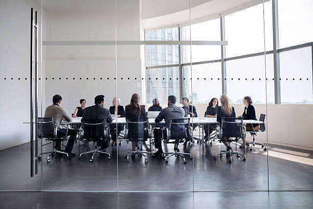 colleagues at business meeting in conference room - business meeting stock pictures, royalty-free photos & images