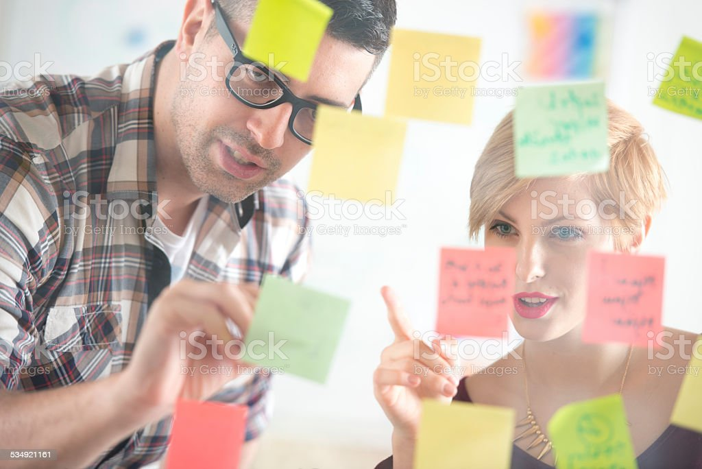 Colleagues attaching sticky notes to a glass partition stock photo