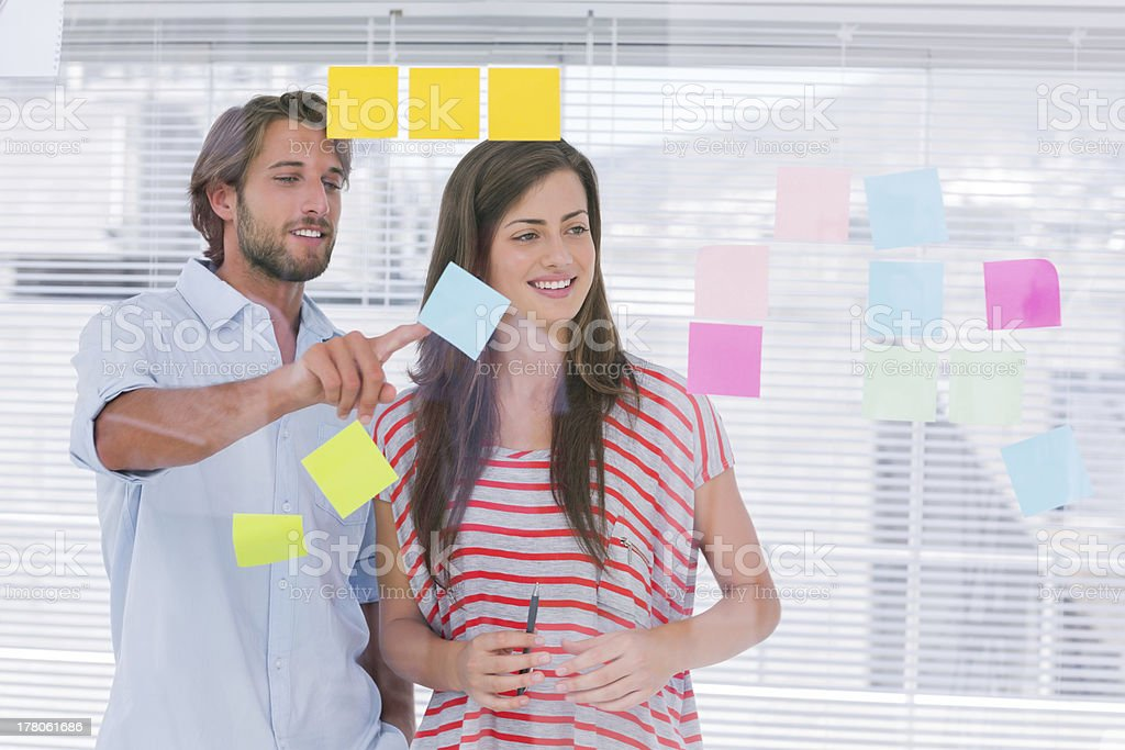 Colleagues brainstorming together by placing sticky notes royalty-free stock photo