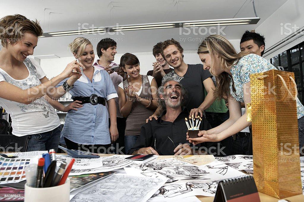 Colleagues celebrating the birthday of their boss royaltyfri bildbanksbilder