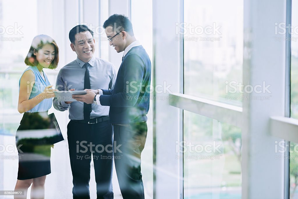 Colleagues chatting in corridor stock photo