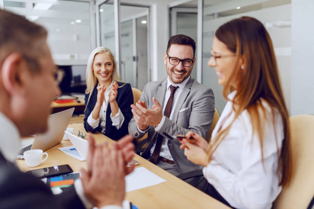 Colleagues clapping to their female colleague for excellent idea while sitting at boardroom. stock photo