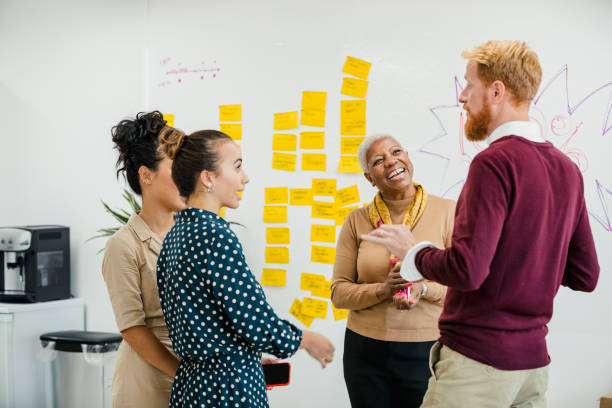 Colleagues Coming Up With Ideas Colleagues standing in a small group discussing something and laughing while are standing in front of a whiteboard. southeast england stock pictures, royalty-free photos & images