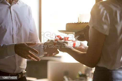 istock Colleagues congratulating coworker receiving gift box and birthday cake, closeup 1085714020