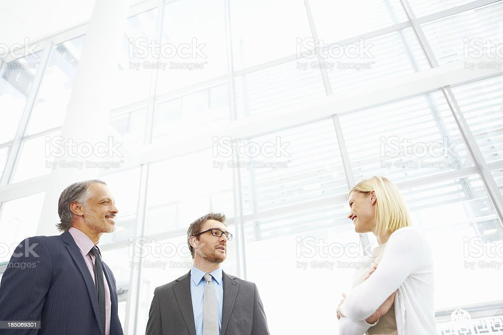 Colleagues conversing in office lobby - Copyspace royalty-free stock photo