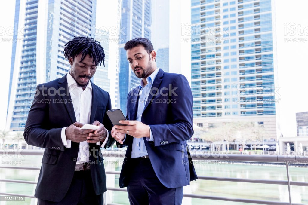 Colleagues discussing a business proposal using a smart phone stock photo