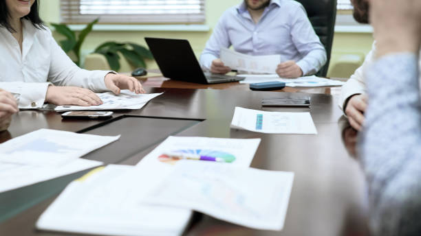 Colleagues discussing data in business meeting, sharing statistic charts, team - foto stock