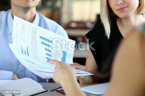Selective focus on business documents. Group of corporate working people negotiating new startup. Man and women looking at graphs and important papers. Restaurant interior