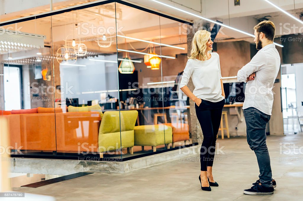 Colleagues discussing ideas in modern office stock photo