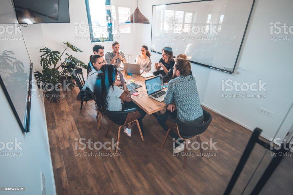 Kolleginnen und Kollegen diskutieren im Sitzungssaal während der Sitzung – Foto