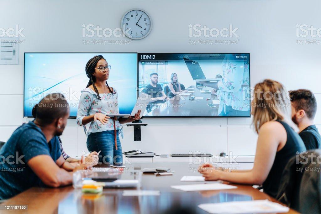 Kollegen diskutieren im Besprechungsraum während der Videokonferenz - Lizenzfrei Arbeiten Stock-Foto
