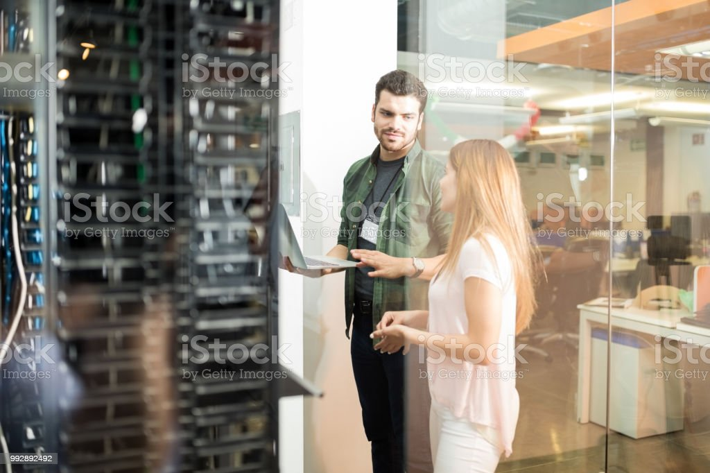Colleagues discussing in office server room stock photo