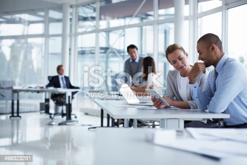 Business colleagues discussing over digital tablet at desk in office