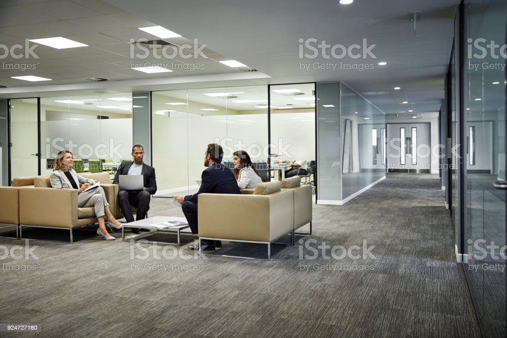 Kolleginnen und Kollegen diskutieren Strategie in Lobby im Büro – Foto