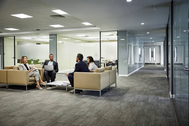 kolleginnen und kollegen diskutieren strategie in lobby im büro - bodenleuchten stock-fotos und bilder