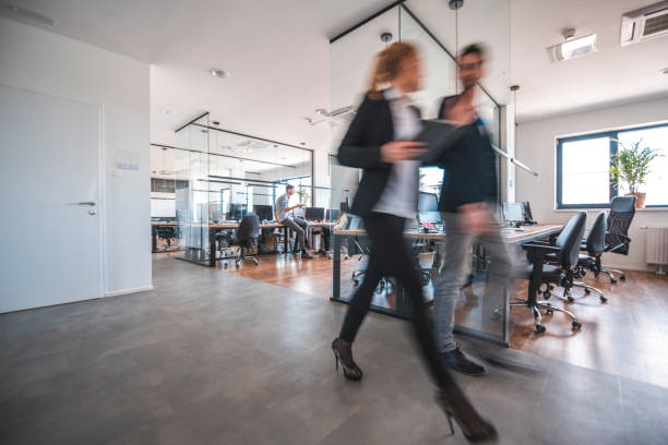 colleagues discussing while walking in office - incidental people stock pictures, royalty-free photos & images