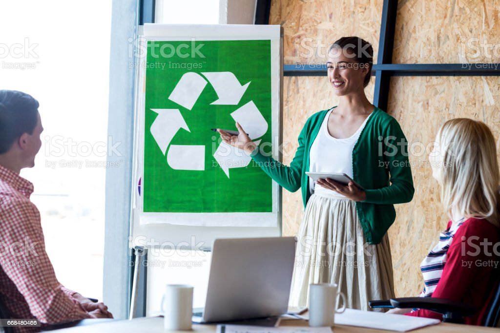 Colleagues discussing with recycling sign on white board - Royalty-free 18-19 Years Stock Photo