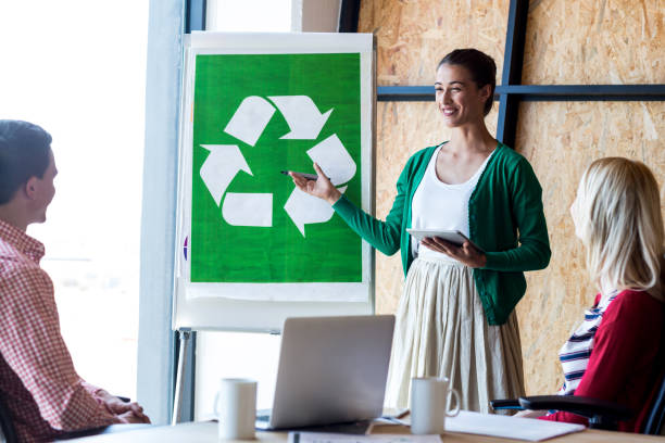 colleagues discussing with recycling sign on white board - responsible business stock photos and pictures