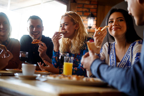 colleagues enjoying pizza together - pizzeria stock photos and pictures